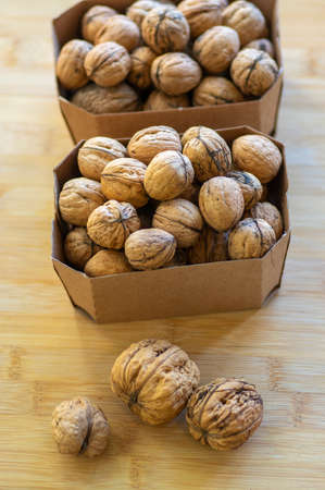 Walnuts on table in hard shells, group of dry ripened fruits in brown cardboard boxes, harvested healthy food ingredients ready for baking and cooking