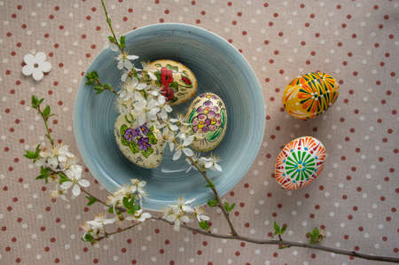 Homemade handmade painted Easter eggs in blue bowl on spotted tablecloth decorated with prunus spinosa blackthorn sloe white flowering branch, wooden flowers, green leaves
