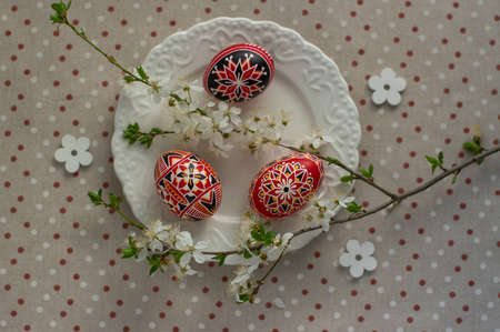 Homemade handmade painted Easter eggs on white plate on spotted tablecloth decorated with prunus spinosa blackthorn sloe white flowering branch, wooden flowers, green leaves Standard-Bild
