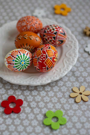 Homemade handmade painted Easter eggs on white plate dish on tablecloth with white petal flowers, Eastertime decoration