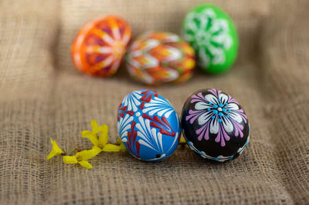 Homemade handmade wax and painted Easter eggs jute textile beige background, Eastertime decoration, five colorful objects and Forsythia yellow flowering branch