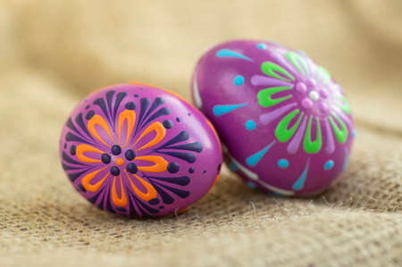 Homemade handmade wax and painted Easter eggs jute textile beige background, Eastertime decoration, two colorful objects Banque d'images