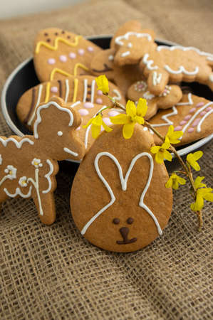 Easter holiday cookies servet on dish on the table with jute tablecloth, group of color painted gingerbread sweets, spring holidays tasty decoration