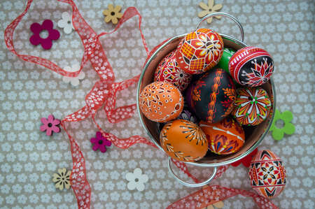 Homemade handmade painted Easter eggs in decorative old pink color tin on flowered tablecloth, springtime holidays, decorative flowers spread around and ribbons