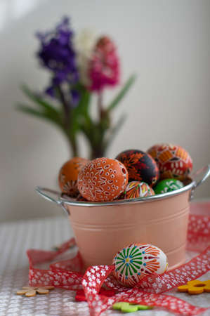 Homemade handmade painted Easter eggs in decorative old pink color tin on flowered tablecloth, springtime holidays and flowering plant hyacinth