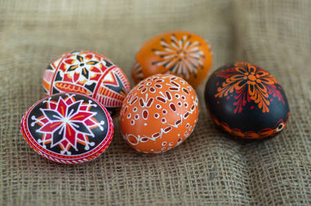Homemade handmade wax and painted Easter eggs jute textile beige background, Eastertime decoration, five colorful objects