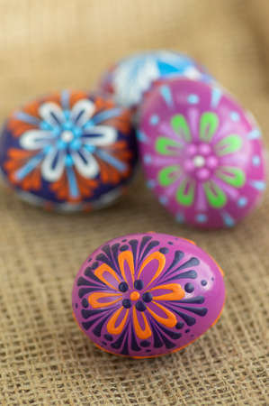 Homemade handmade wax and painted Easter eggs jute textile beige background, Eastertime decoration, four colorful objects