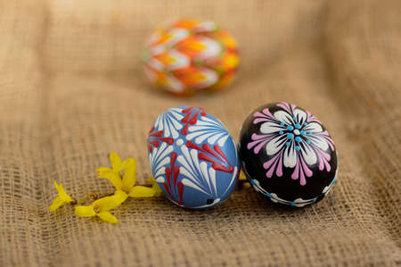 Homemade handmade wax and painted Easter eggs jute textile beige background, Eastertime decoration, three colorful objects and Forsythia yellow flowering branch Banque d'images
