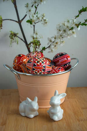 Homemade handmade painted Easter eggs in decorative old pink color tin on wooden table, springtime holidays flowering branches