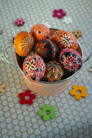 Homemade handmade painted Easter eggs in decorative old pink color tin on flowered tablecloth, springtime holidays, decorative flowers spread around Banque d'images