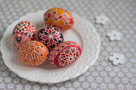 Homemade handmade painted Easter eggs on white plate dish on tablecloth with white petal flowers, Eastertime decoration Banque d'images