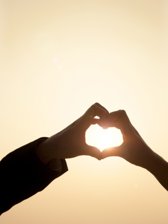 Shiloutte of two hands join to form a heart shape with sun beam inside the heart photo