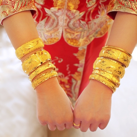 numerous: Numerous golden wedding bangles on Chinese brides arms