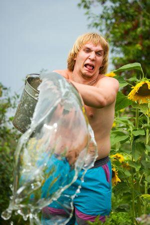 Young man splashing water to frog.  photo