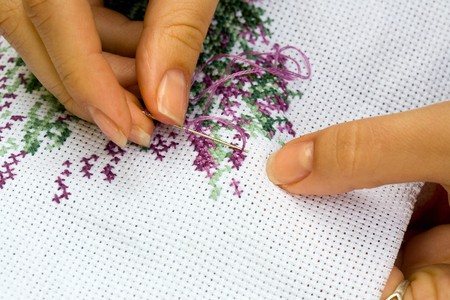 fancywork: Fingers of young women, cross embroidery. Stock Photo