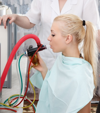 Young woman on the inhalation procedure  at the resort