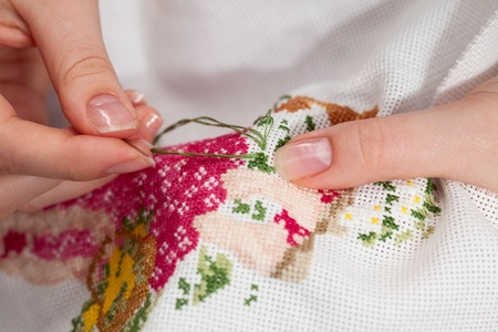 embroider: Woman hands doing cross-stitch  A close up of  embroidery