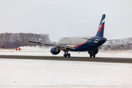 The plane accelerates on the winter runway