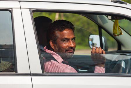 Indian man in car smiling