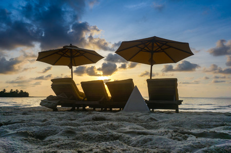 Sandy tropical beach with deck chairs when sunset photo