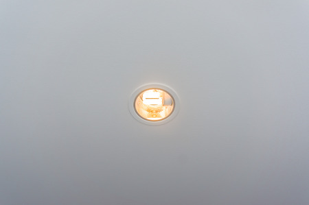 Ceiling downlight on white ceiling, warm light photo
