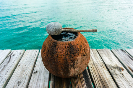 water jar on wooden floor with sea background photo