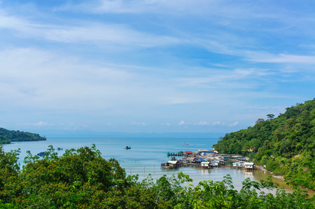 Fisherman village in thailand sea with blue sky and mountain photo