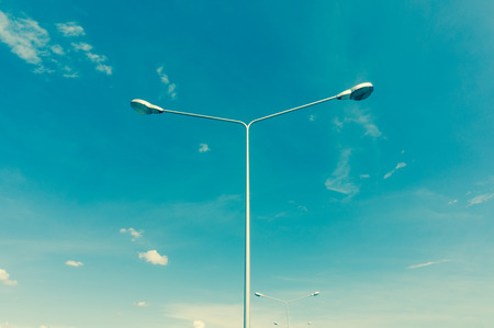 electric avenue: street lamps aligned with blue sky in background, cross process style Stock Photo