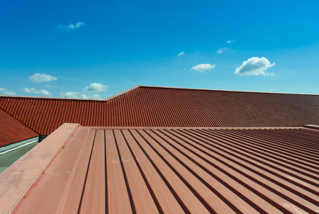 metales: Detalle arquitectónico de techos de metal en la construcción comercial con fondo de cielo azul