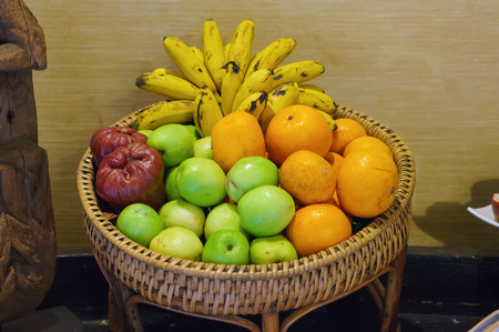 jujube fruits: Fresh organic fruits, citrus, jujube, bananas, placed on a basket weave, with soft light  and shadow
