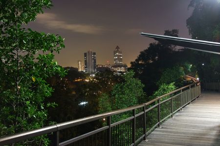 kent: Lighted canopy walk with buildings and trees at the background, by night Stock Photo