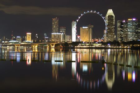 singapore building: View of a Ferris wheel with surrounding buildings and a bridge, by Marina Bay at night Stock Photo