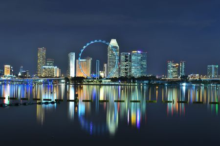 marina: Cityscape around a Ferris Wheel, known as Singapore Flyer, by night Stock Photo