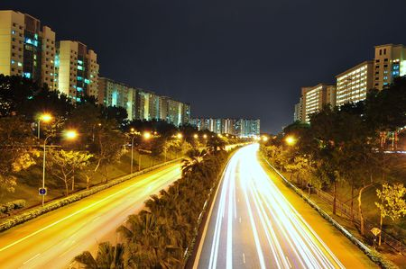 An expressway (TPE - Tampines Expressway) with lights that come from moving cars, surrounded by apartments, at Punggol area (Singapore) Banque d'images