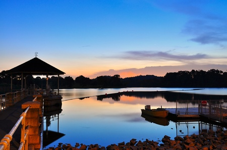 pierce: Colourful sunset and the reflection on Lower Pierce reservoir (Singapore), with a gazebo, boat and jetty as foreground Stock Photo