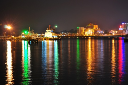 Johore Strait with very colourful light reflection, with causeway and some Johor buildings at the background Stock Photo