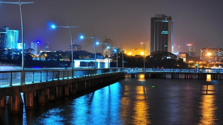 L-shaped fishing jetty in Woodlands Waterfront (Singapore) by night with bluish and yellowish light reflections