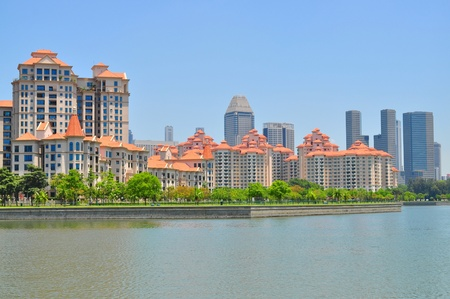 Apartments and buildings by the river at Kallang Basin, under the clear blue sky photo