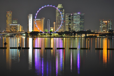 singapore building: Cityscape with Ferris wheel and light reflection on the water, by night, at Marina Bay, Singapore Stock Photo