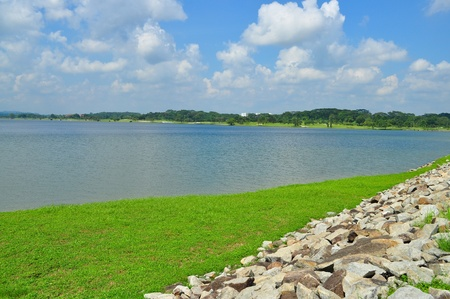 reservoir: Lower Seletar Reservoir (Singapore) with green pasture and stones in the foreground on a sunny day