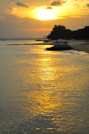 east coast: Bright yellow sunset with its reflection on a beach at East Coast Park, Singapore  Stock Photo