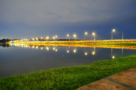 lamp post: Lower Seletar Reservoir surrounded by green grass, road and the lightings Stock Photo