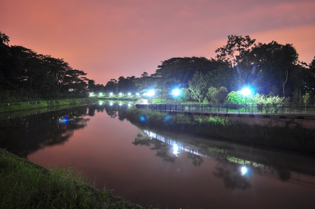 alongside: A lighted walkway alongside the river with reddish sky at night in Sembawang area Stock Photo