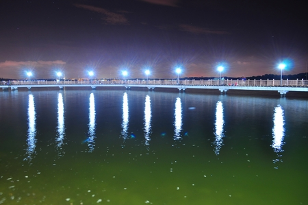 sg: Floating bridge at Changi Beach Singapore by night with slightly starry sky and light reflection on water from lamp post. This bridge is actually a place for people to relax, unwind, and do fishing.