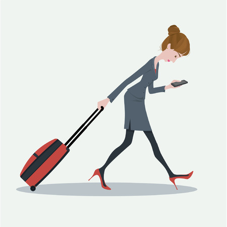 walking away: Young business woman pulling the luggage busy with mobile phone.