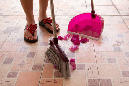 female was sweeping the tile is dry, use a broom. photo