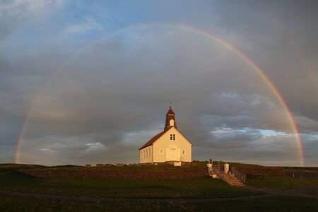 Church Strandarkirkja with rainbow around - a Lutheran (Church of Iceland) parish church in Selvogur, on the southern ocean coast of Iceland, often referred to as the 'miracle church'