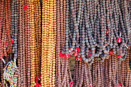 Prayer Mala beads for sale at a market stall in Pashupatinath, Kathmadu, Nepal. Some malas are made in traditional materials such as rudraksha seed, bodhi seed, or yak bone.