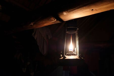 Traditional kerosene lamp hung under a wooden beam in shepherd's hut in mountains