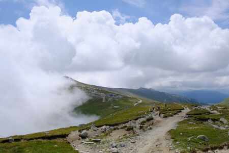 Romania, Bucegi Mountains - road with hiking tourists from Baba Mare to Omul, mountain view Stock Photo